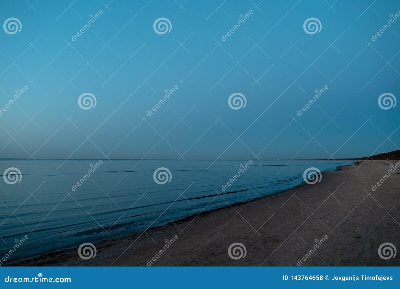 Levendige verbazende zonsondergang in Baltische Staten - de Schemer in het overzees met horizon verlicht door de zon