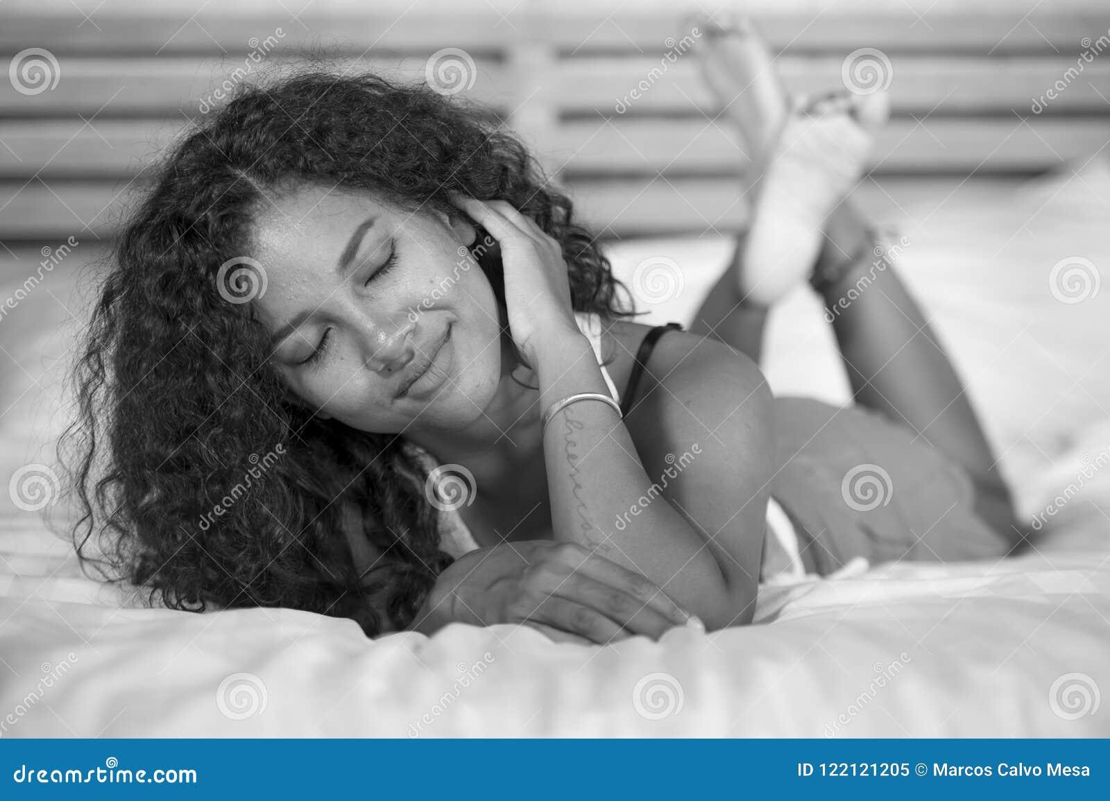 Levensstijl zwart-wit portret van jonge gelukkige en schitterende Spaanse vrouw die sexy en speelse thuis slaapkamer stellen die