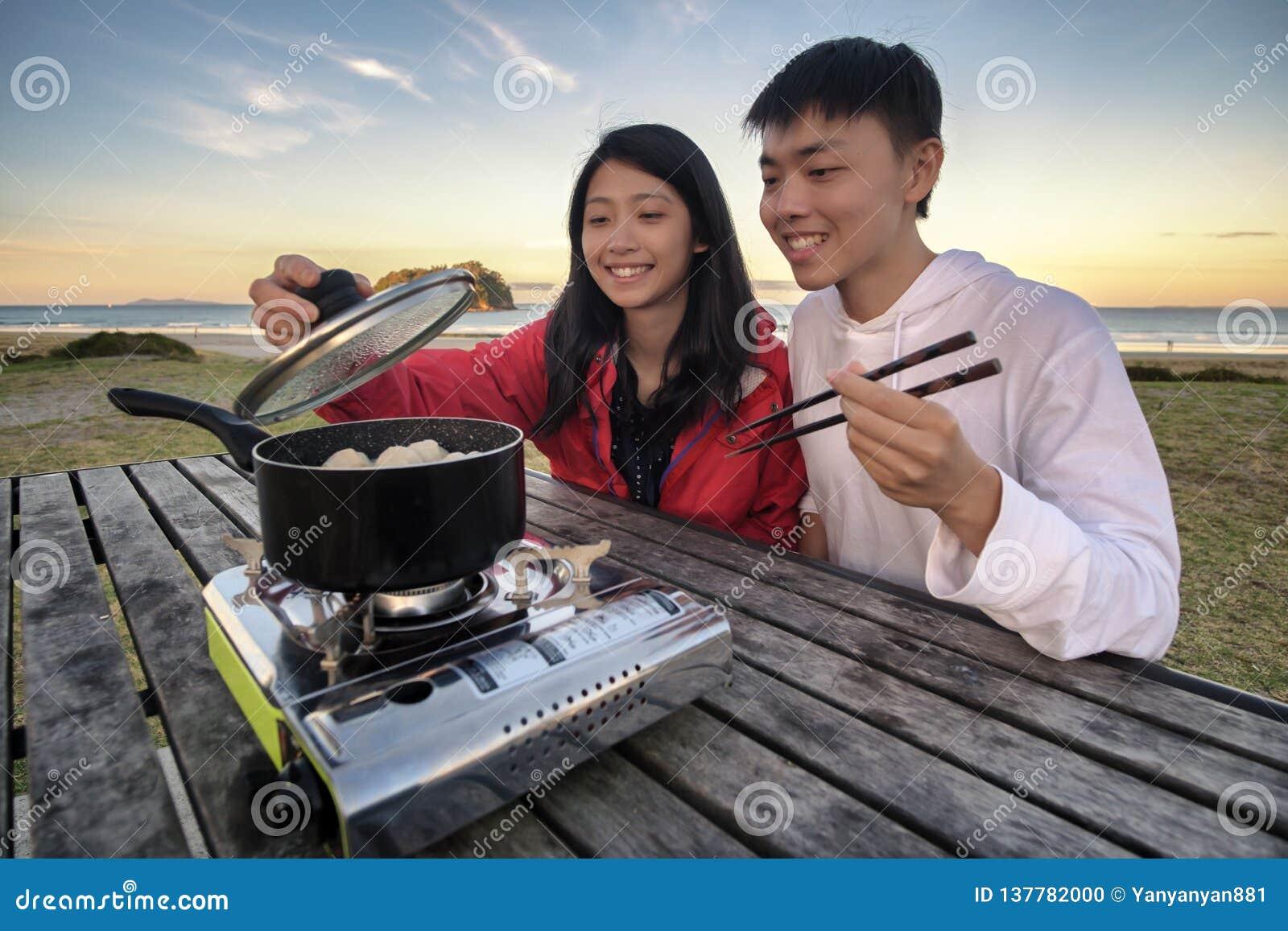 Levensstijlbeeld van jong gelukkig Aziatisch paar die heet pottenfornuis op een lijst openlucht langs strand eten Het beeld van d
