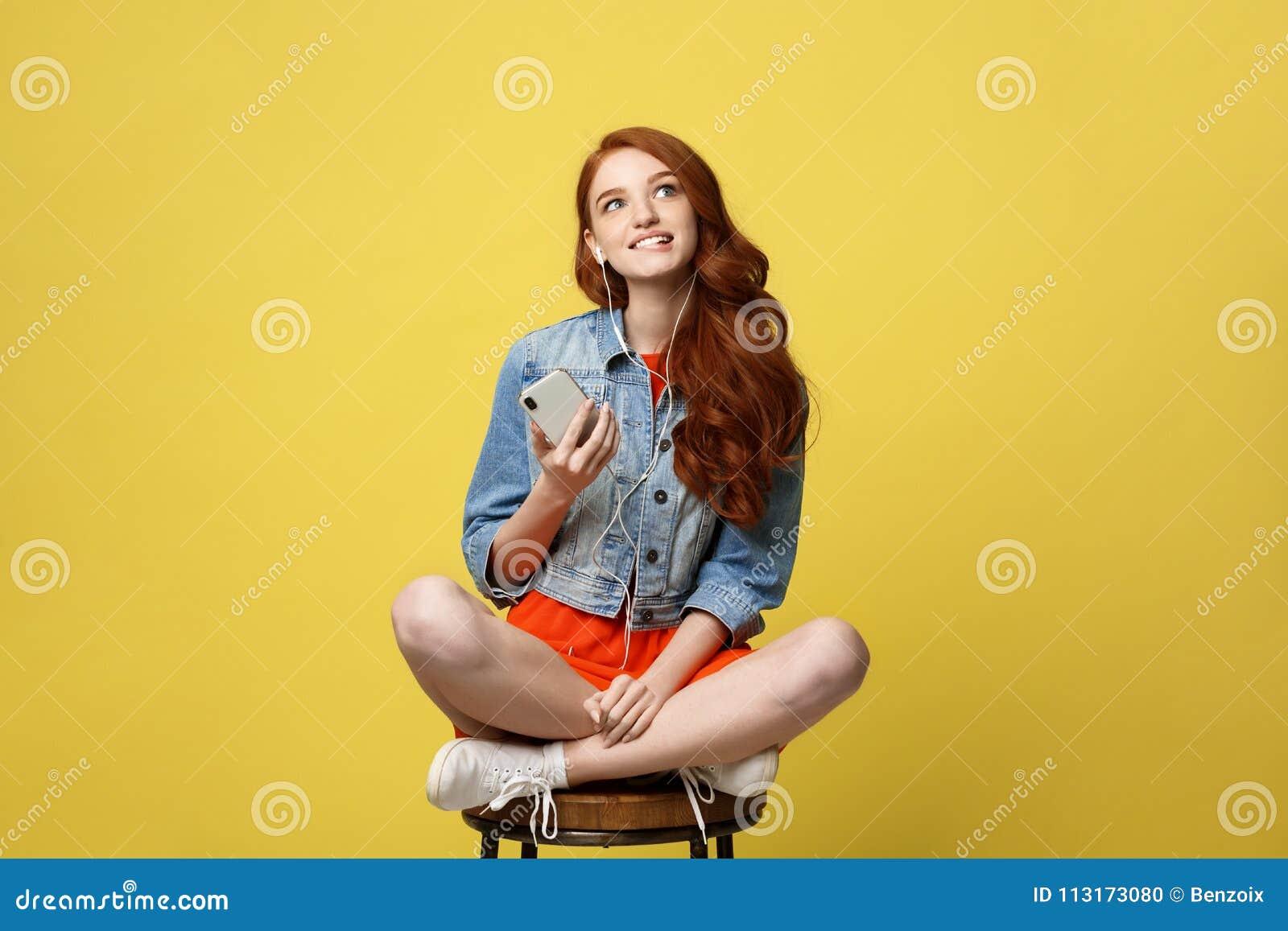 Levensstijlconcept: Het mooie meisje met lang krullend rood haar geniet van luister aan muziek op haar telefoon en zittend op hou