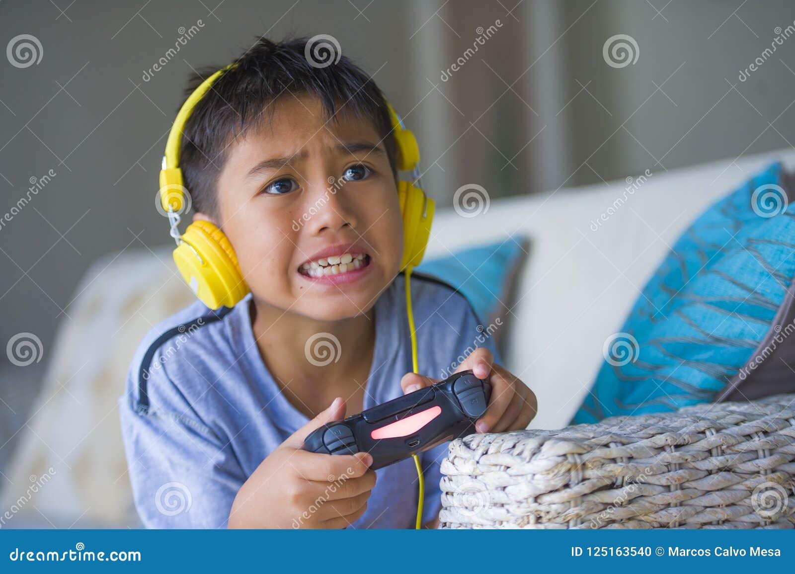Levensstijlportret van jonge Latijn weinig opgewekt jong geitje en gelukkig het spelen videospelletje online met hoofdtelefoons d