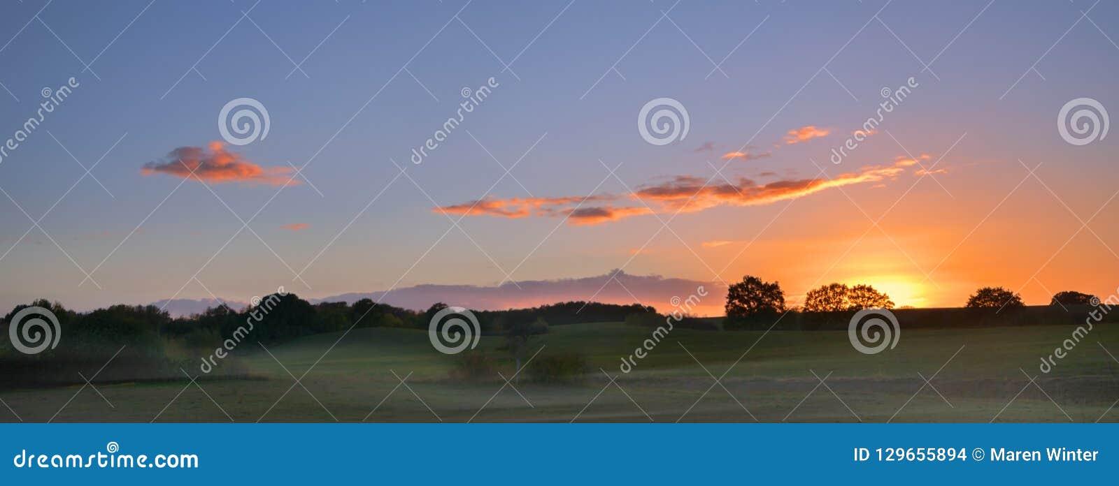 Lever de soleil avec les nuages rougeoyants au-dessus d un paysage rural large avec le montant éligible maximum