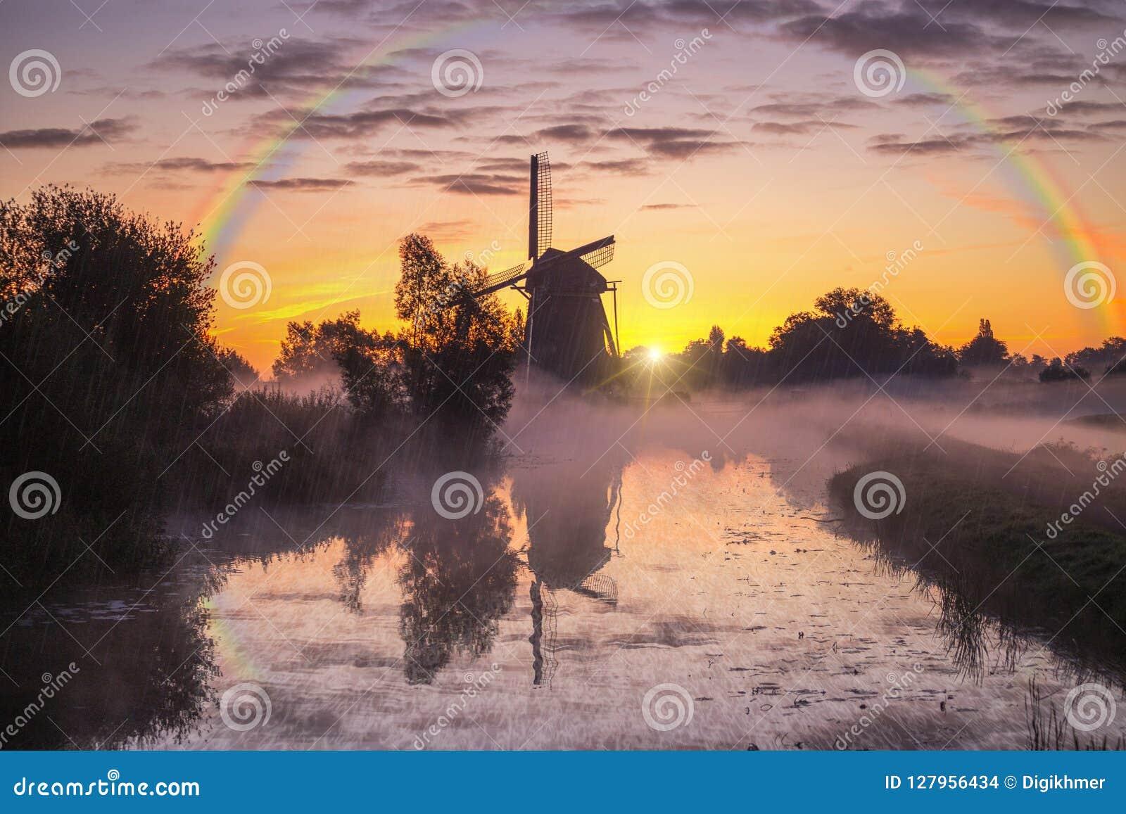 Lever de soleil chaud de moulin à vent brumeux et pluvieux