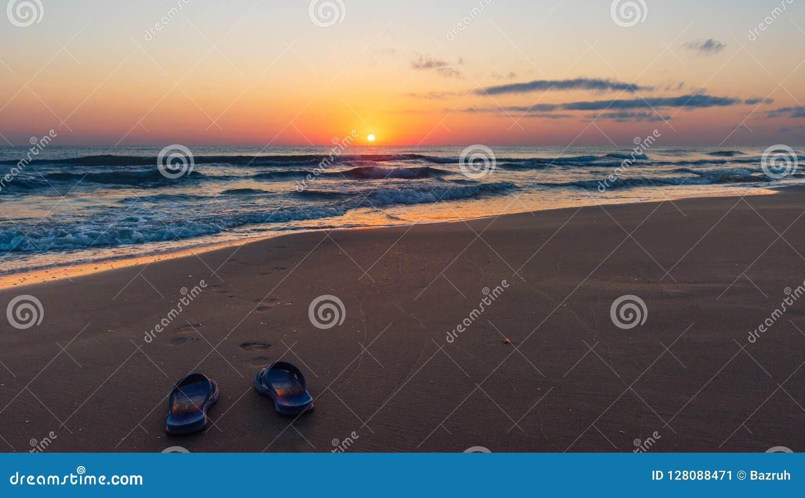 Lever de soleil coloré étonnant en mer, empreintes de pas dans le sable