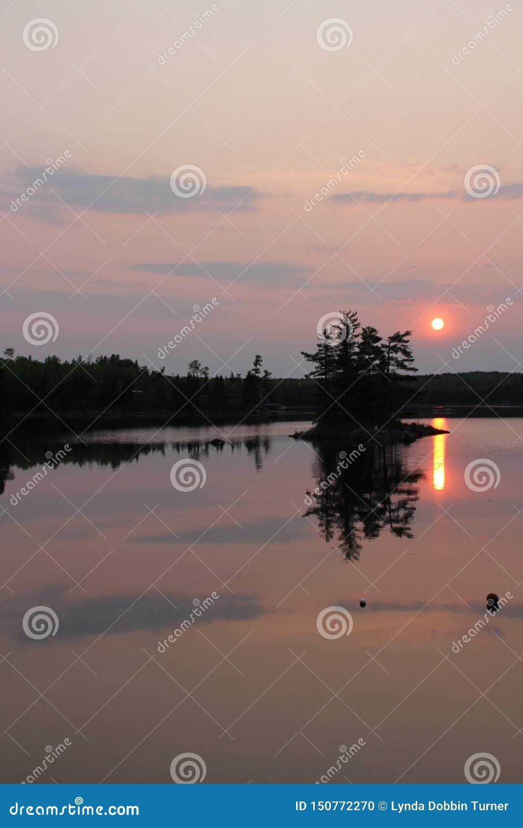 Lever de soleil flou au-dessus de réflexion de lac