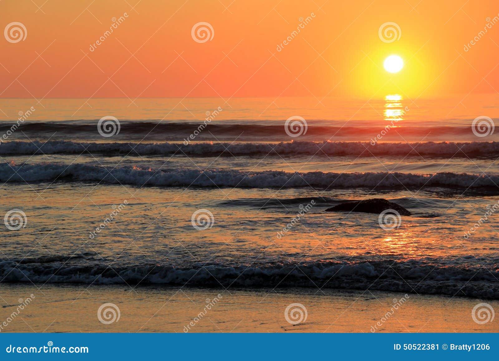 Lever de soleil magnifique au-dessus des roches le long du rivage