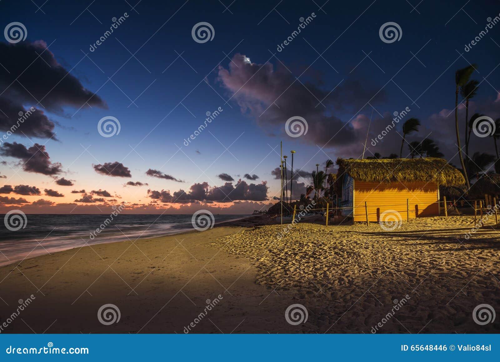 Lever de soleil mystique avec la lune et les étoiles au-dessus de la plage sablonneuse dans Punta
