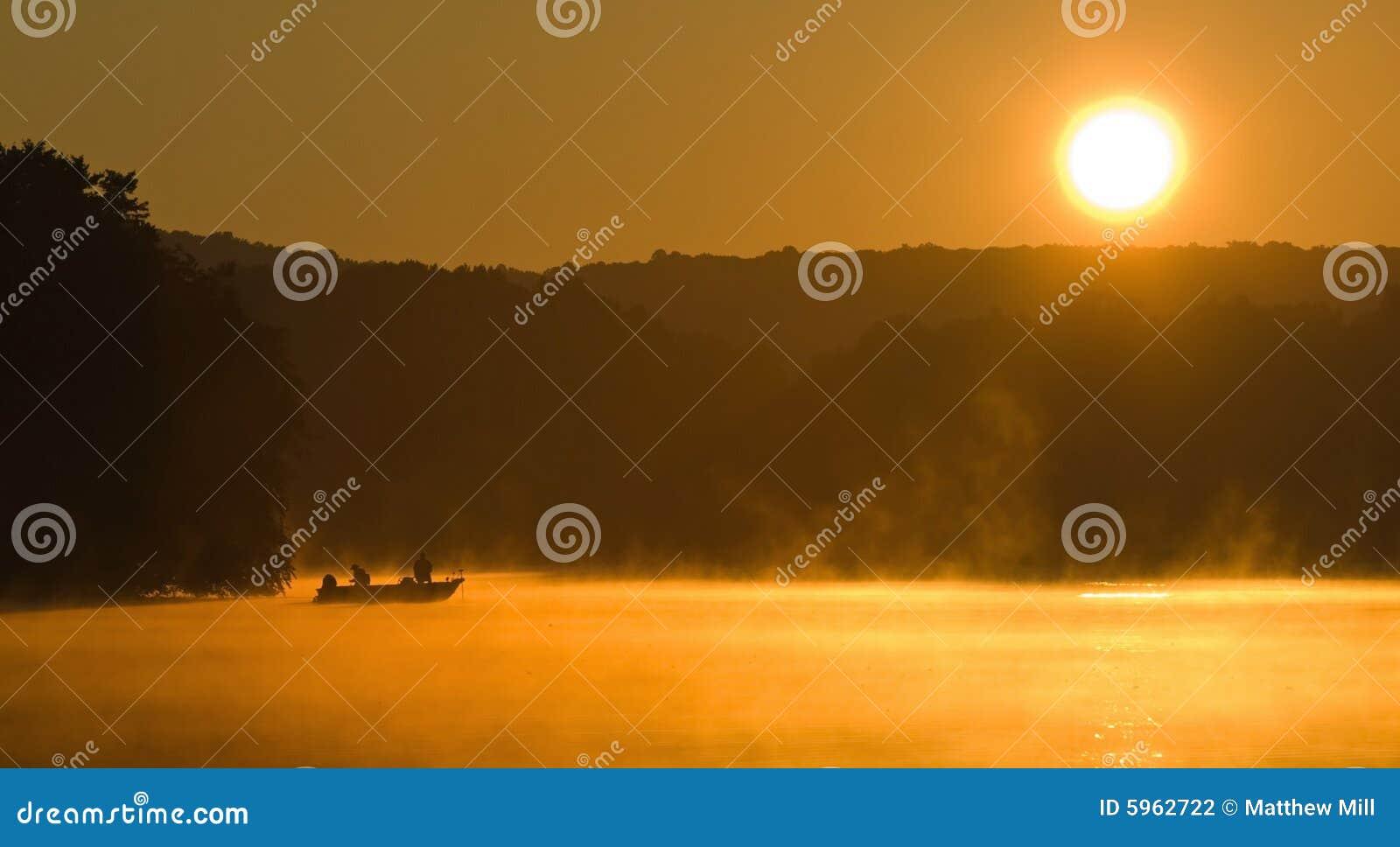 Lever de soleil pêchant sur un lac
