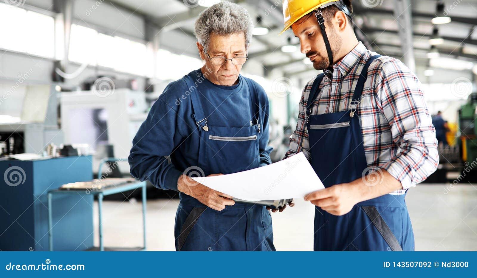 Leverantör med teknikern som kontrollerar på produktion i fabrik