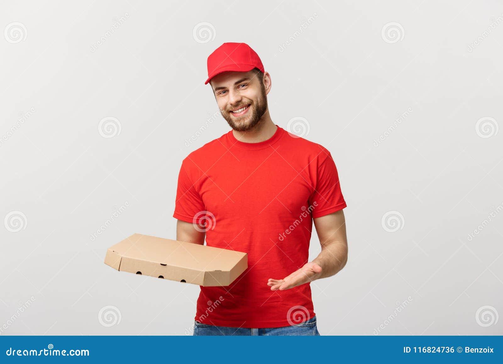 Leveringsconcept: Jonge haapy Kaukasische Knappe die van de de mensenholding van de Pizzalevering de pizzadozen over grijze achte