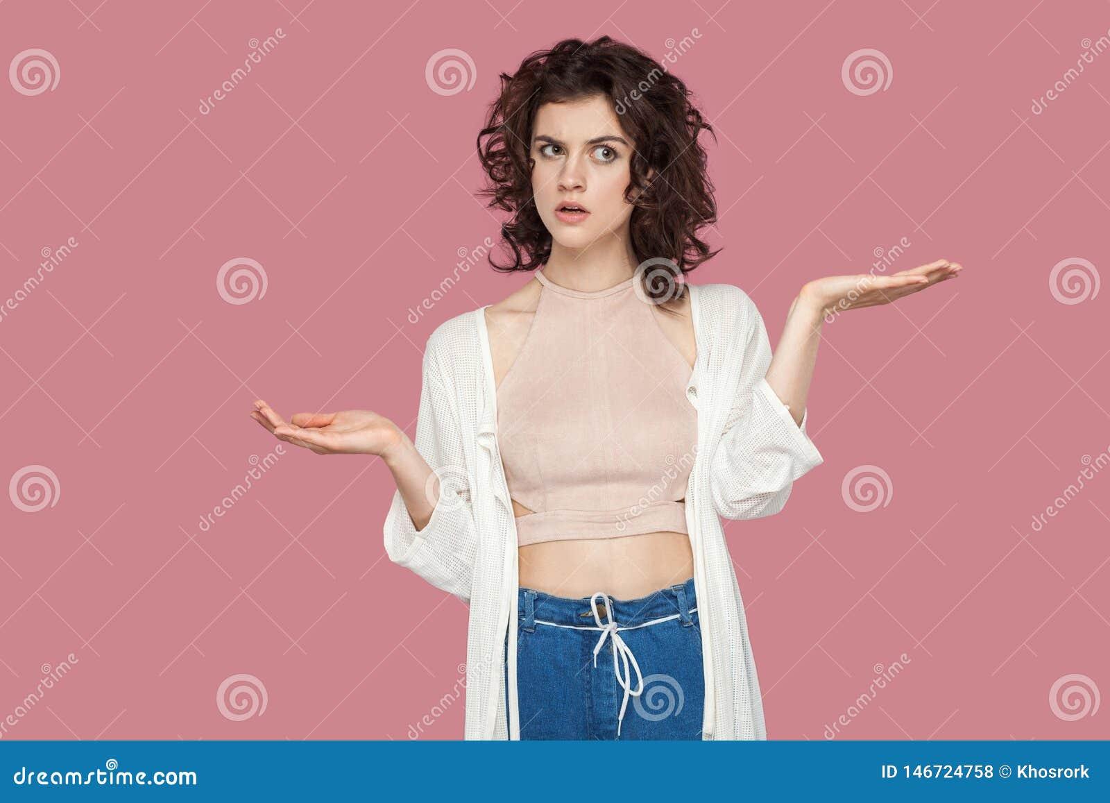 Lewica lub dobro? Portret wątpliwa piękna brunetki młoda kobieta z kędzierzawą fryzurą w przypadkowego stylu pozycji, podnosić rę