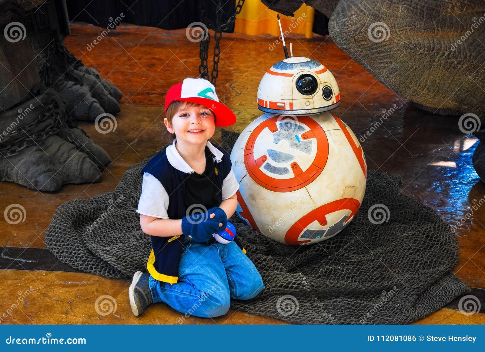 Lexington, Ky США - 11-ое марта 2018 - Lexington шуточный & мальчик жулика игрушки молодой представляет с механически роботом BB8