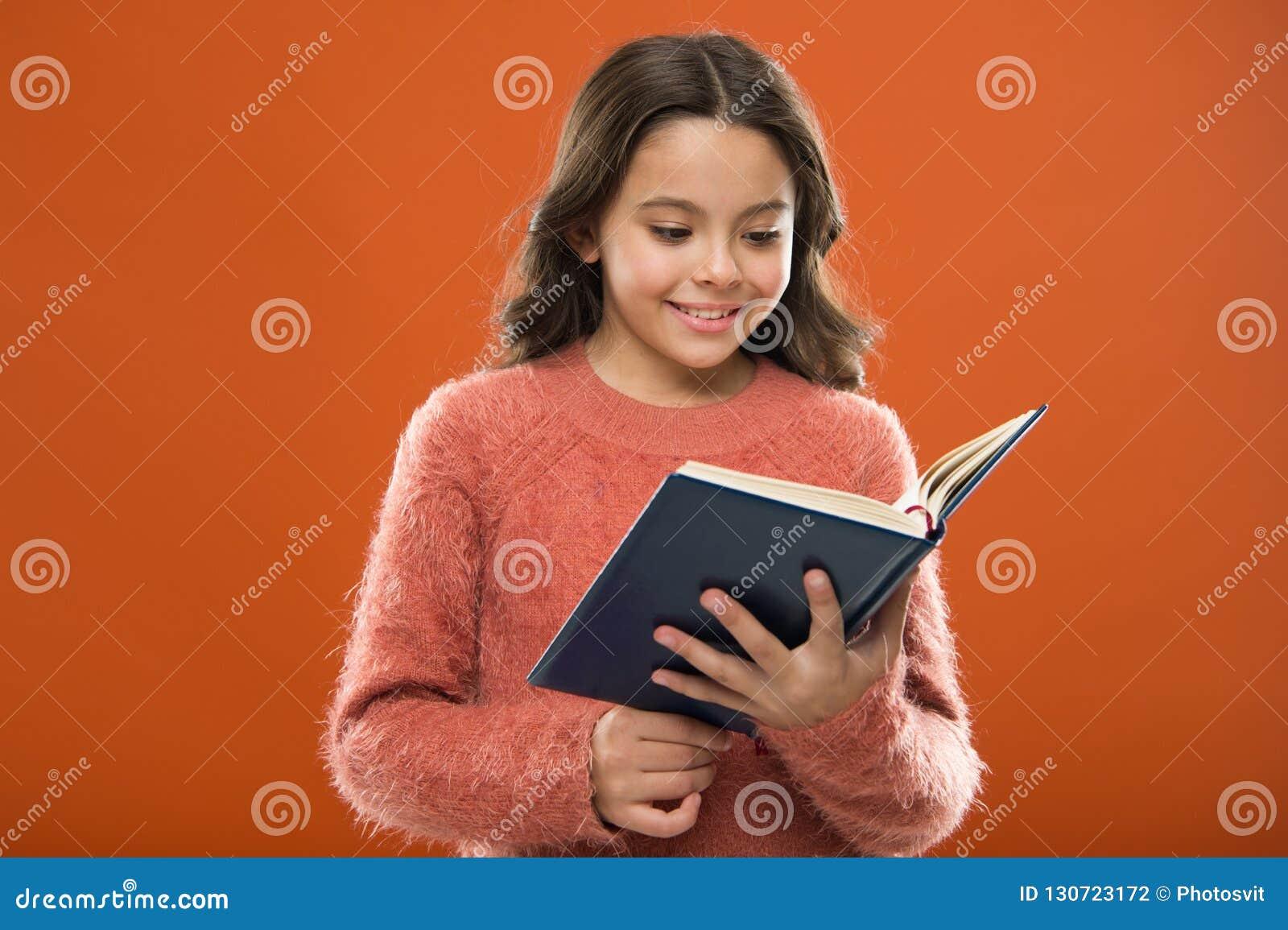Lezingsactiviteiten voor jonge geitjes Het gelezen verhaal van de meisjesgreep boek over oranje achtergrond Het kind geniet van l