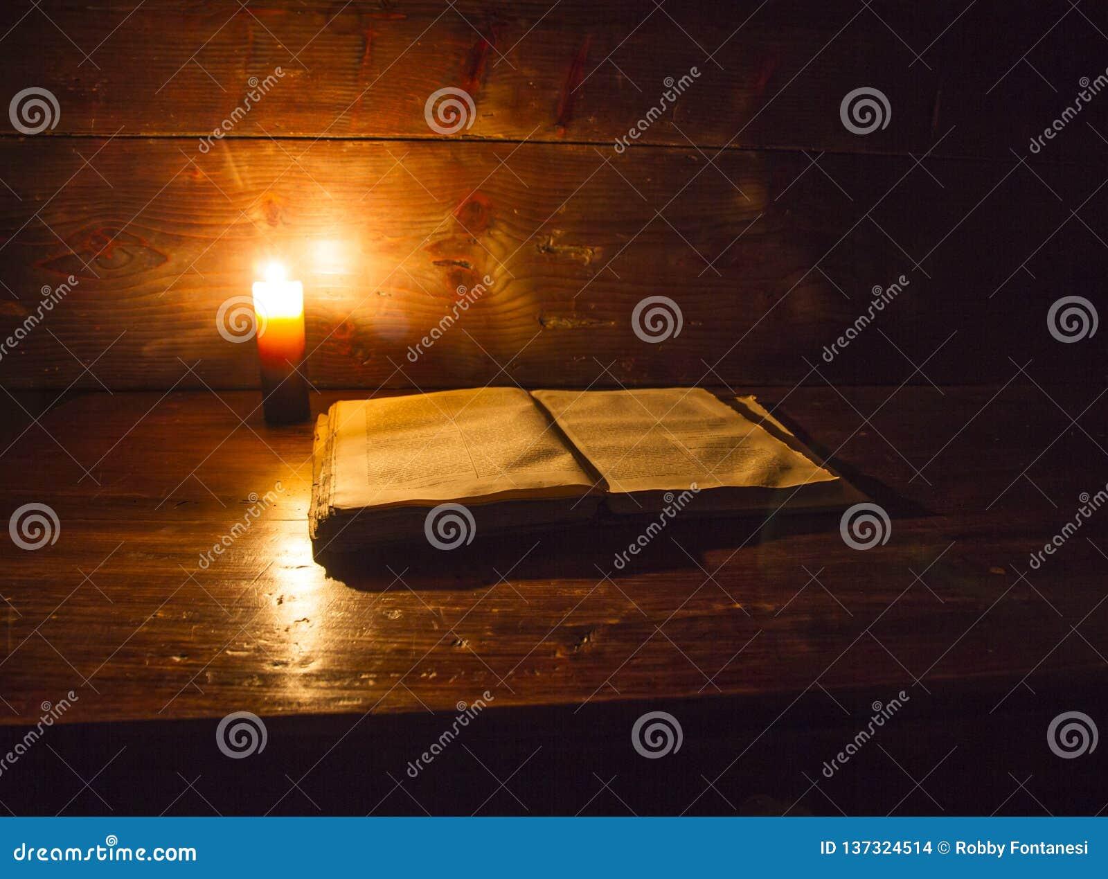 Lezingsscène in oudheid: een oud boek die op geruïneerde houten die lijst leunen door een kaars op een houten achtergrond wordt a