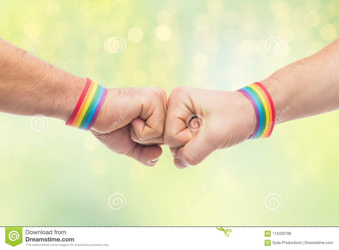 Hands with gay pride wristbands make fist bump