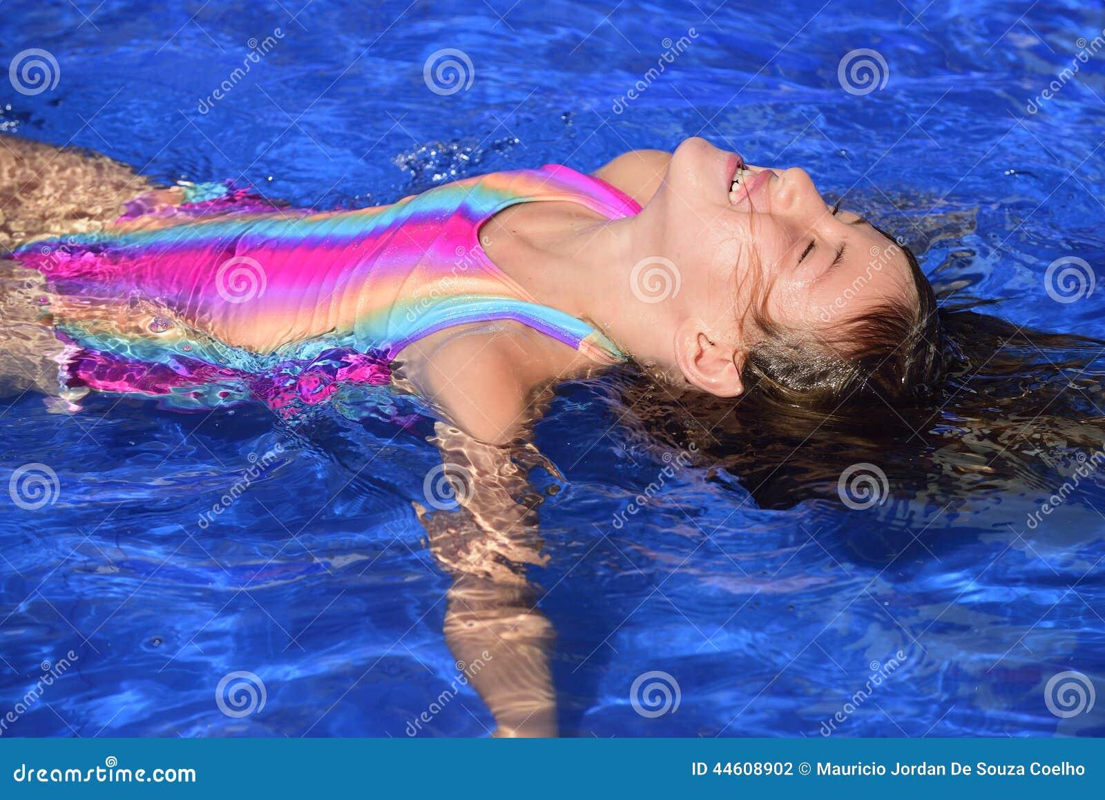 Lições da natação: Criança que aprende flutuar