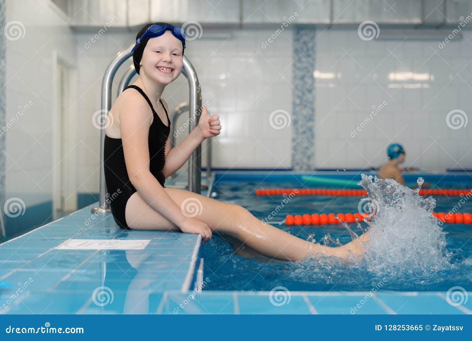 Lições da natação para as crianças na associação - retrato de uma menina branco-descascada bonita em um maiô e em um tampão da na