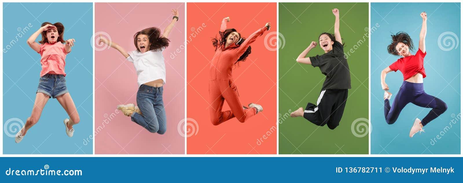 Liberdade em mover-se Jovem mulher bonita que salta contra o fundo alaranjado