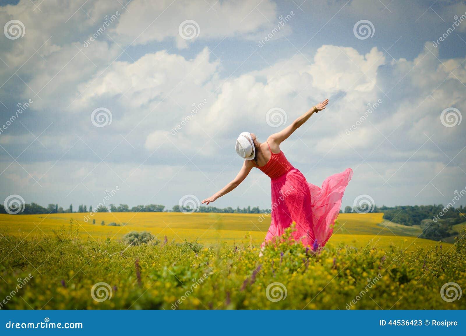 Libertà soleggiata: immagine di bella giovane donna bionda in vestito rosa divertendosi dancing sullo spazio verde della copia de