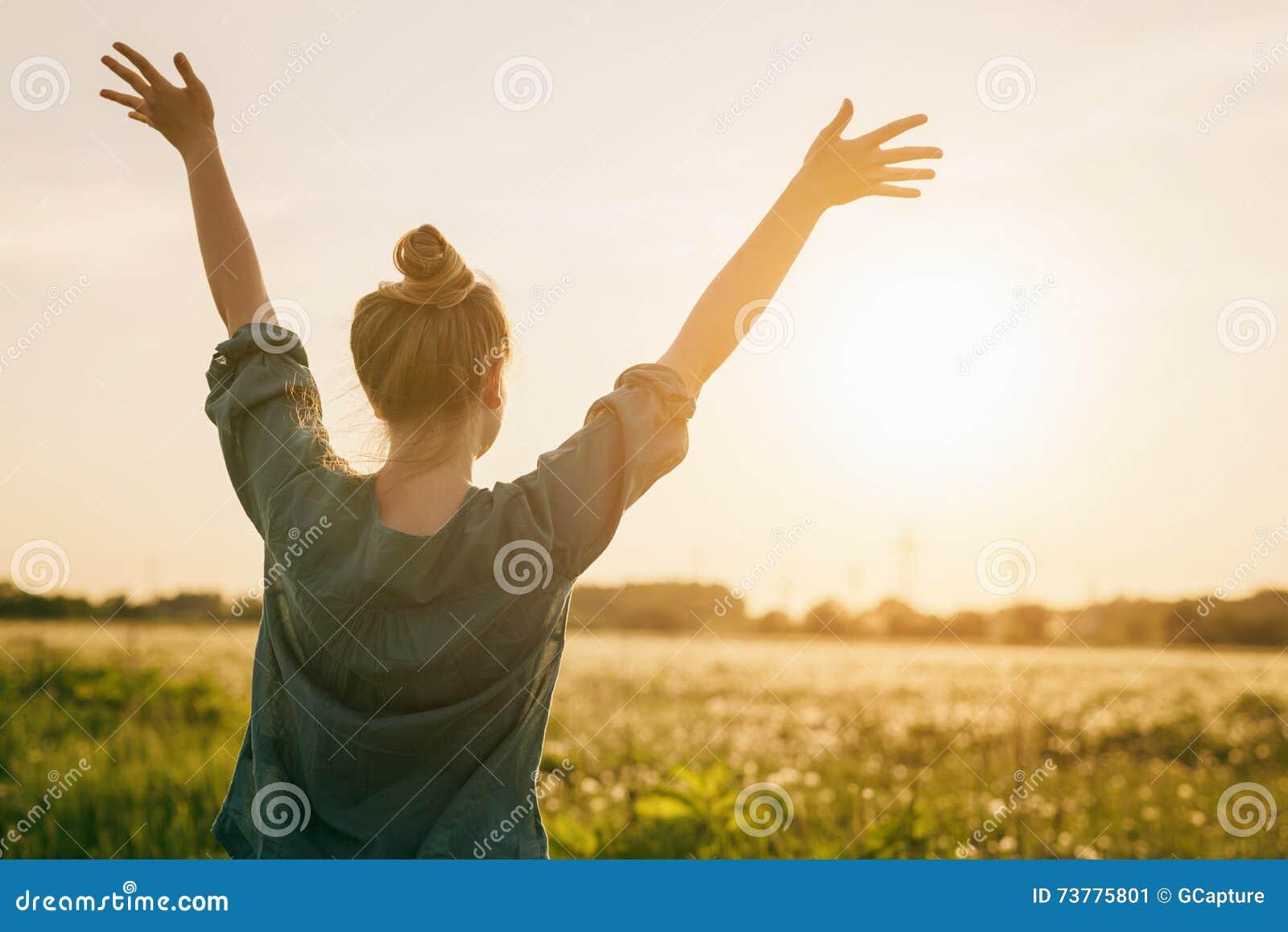 Libertad adolescente femenina de la sensación del soporte de la muchacha con los brazos estirados al cielo