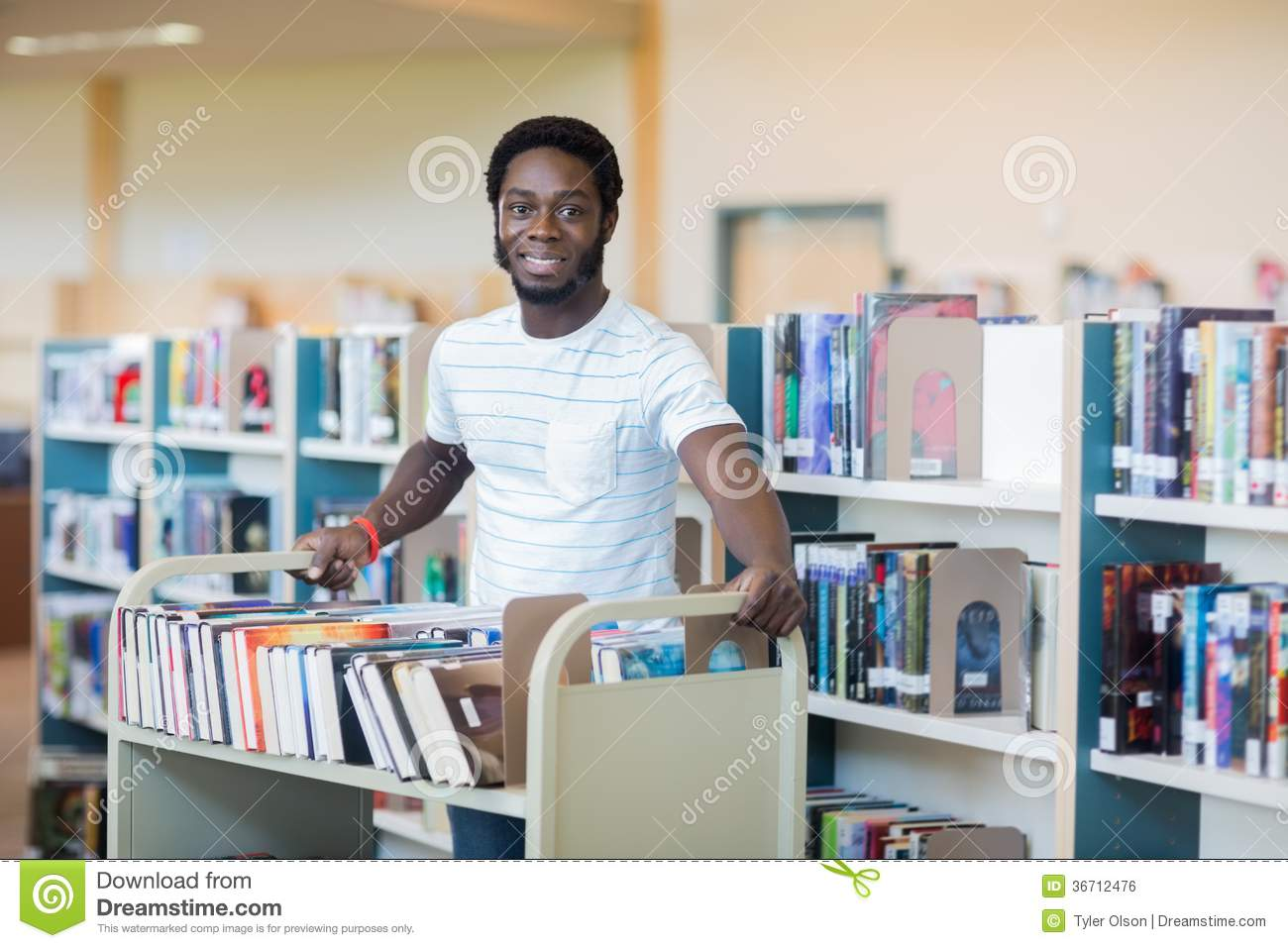 Librarian With Trolley Of Books In Library