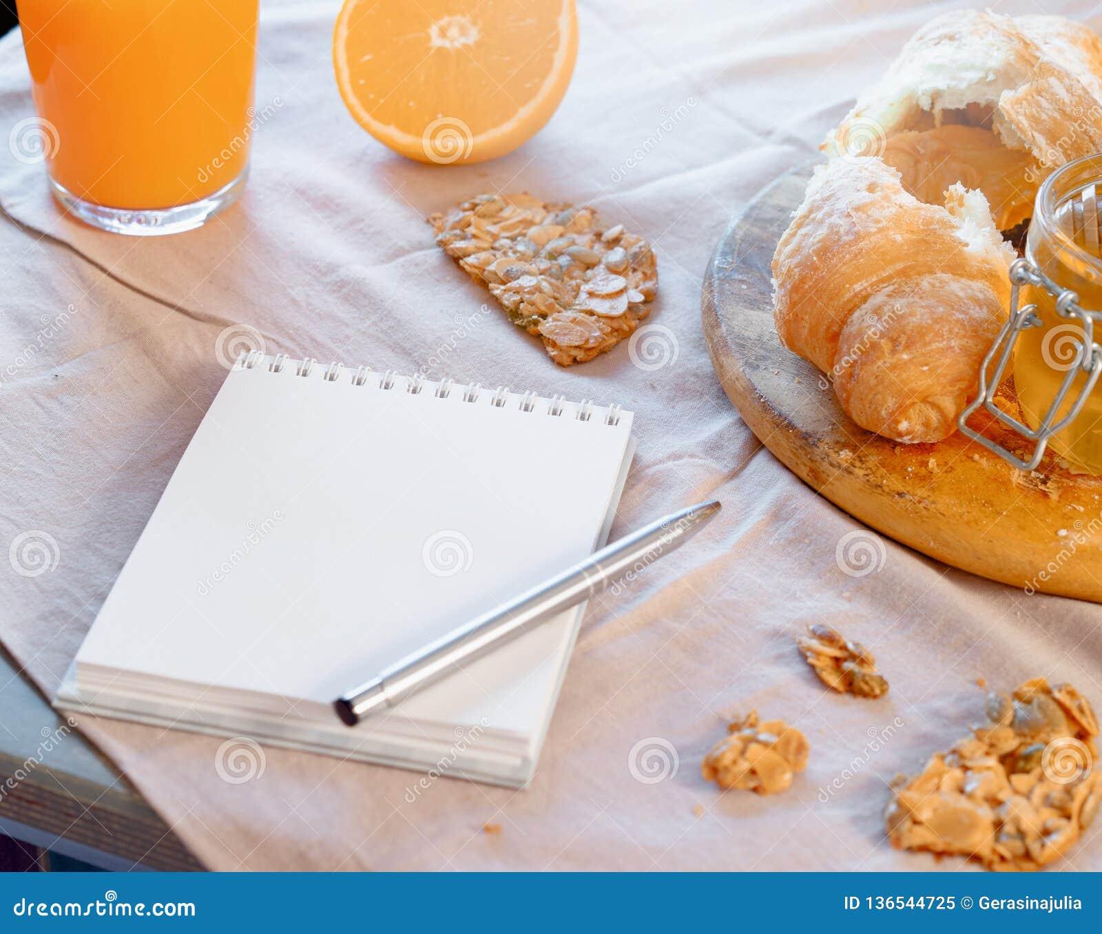 Libreta en blanco cerca de la galleta del cruasán y de la avena Planeamiento sano del desayuno y de la mañana