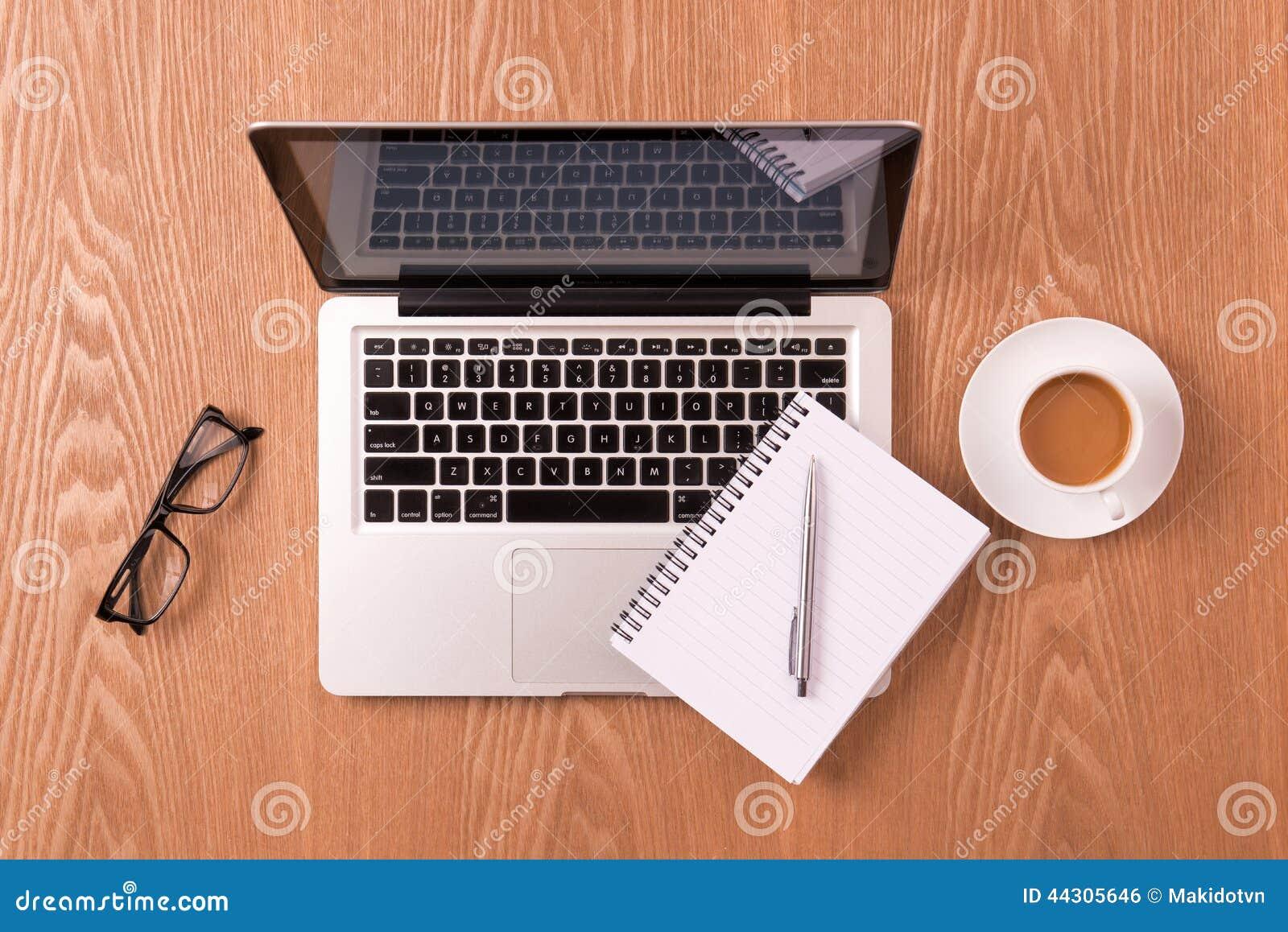 Libreta en blanco sobre la taza del ordenador portátil y de café en la tabla de madera