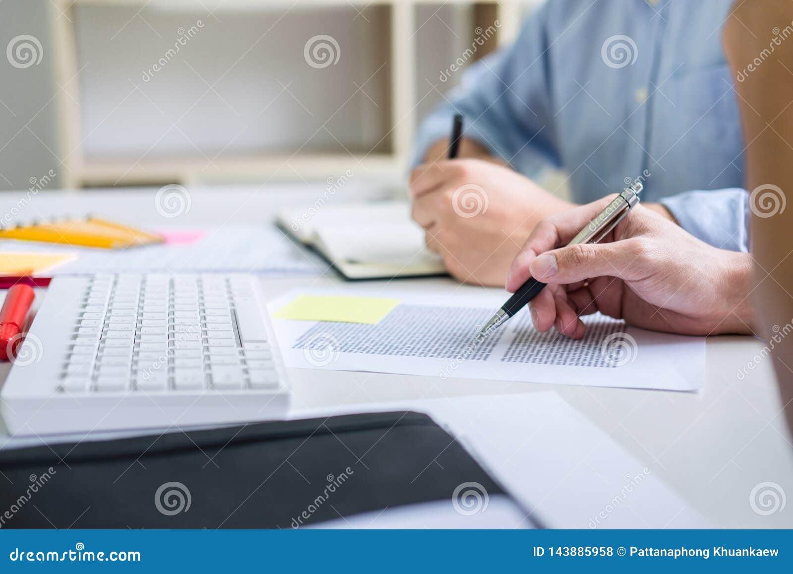 Libri dell istitutore con gli amici, seduta dell uomo indicanti studio insieme allo scrittorio con gli esami dei compagni di clas