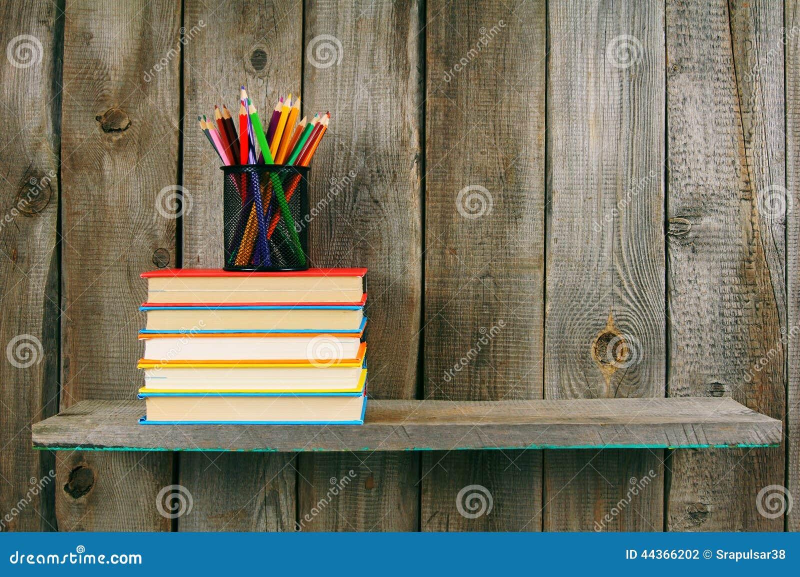 Libri e matite su uno scaffale di legno