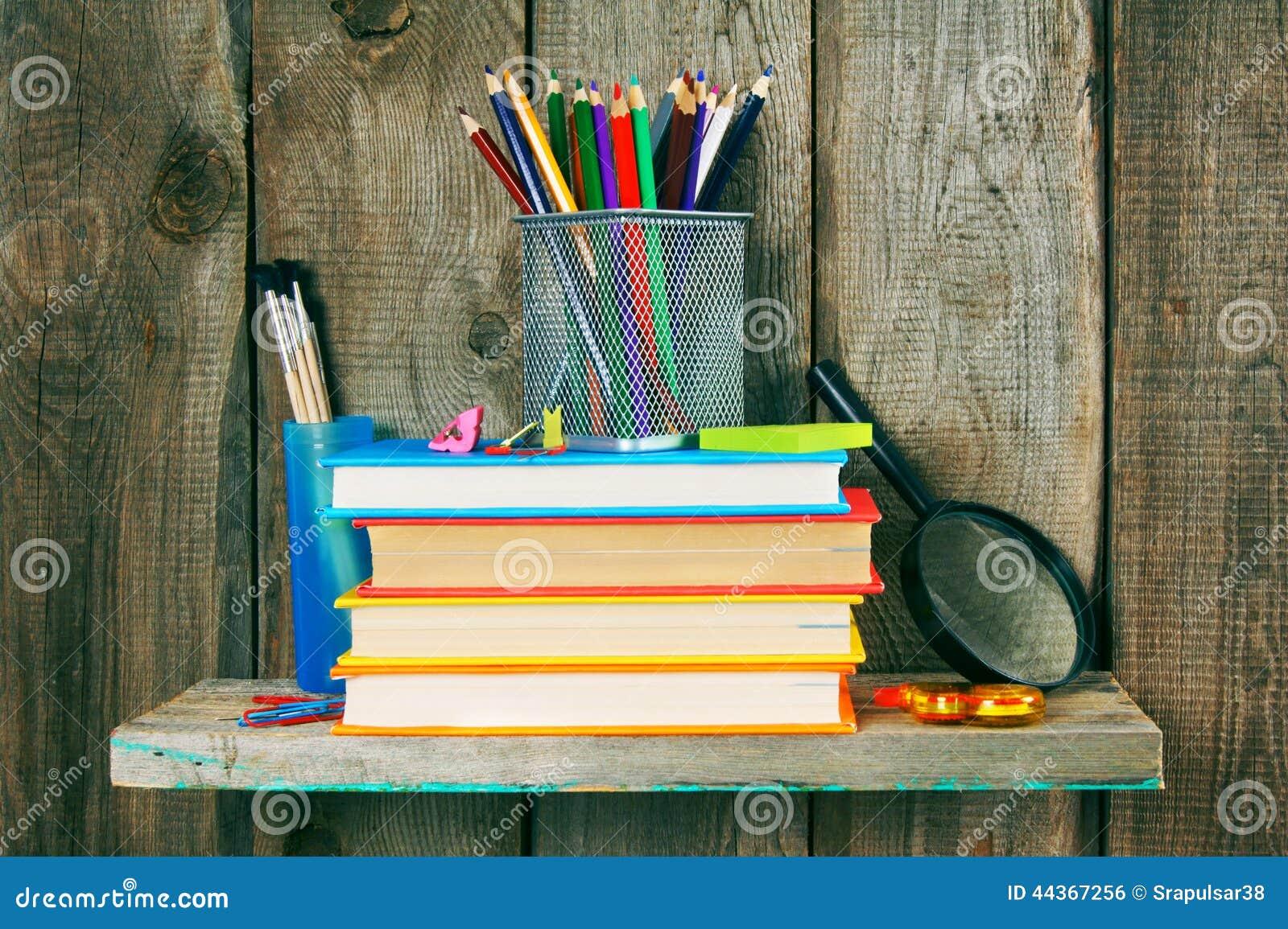 Libri e strumenti della scuola su uno scaffale di legno
