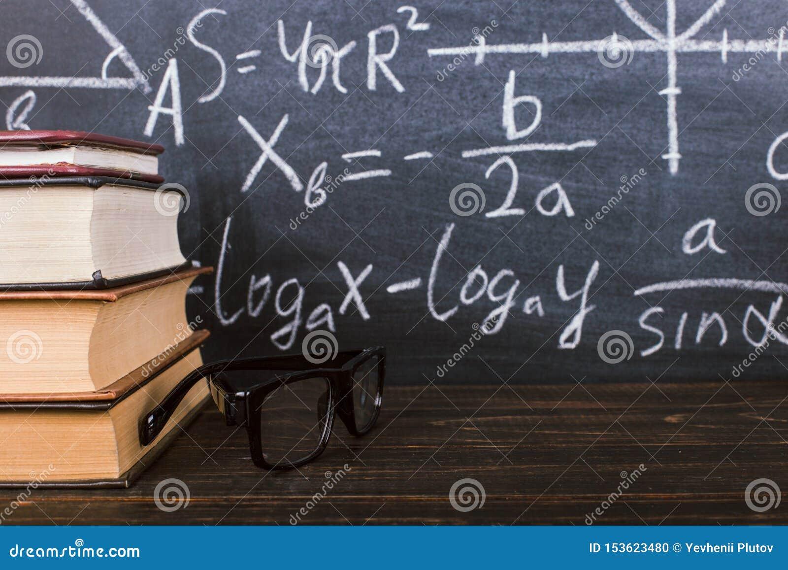 Libri su una tavola di legno, contro lo sfondo di un bordo di gesso con le formule Teacher' concetto di giorno di s e di nuo