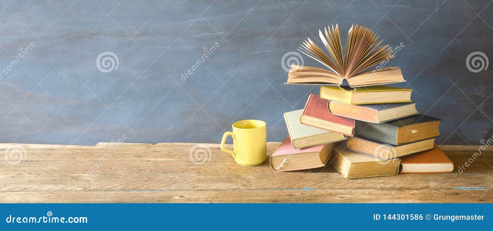Libro abierto en una pila de libros y de una taza de caf? Lectura, aprendiendo, educación, literatura, panorama,