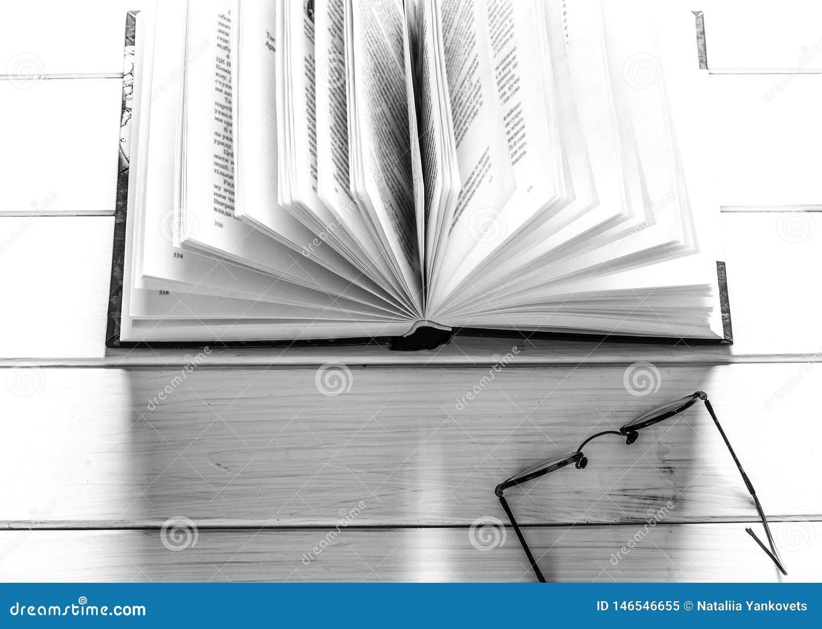 Libro abierto listo para leer mentiras en una tabla de madera blanca al lado de los vidrios redondos viejos