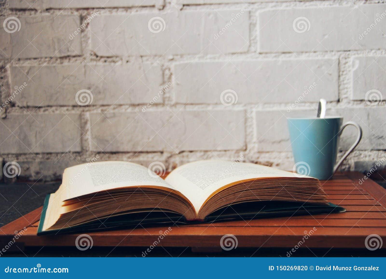 Libro aperto accanto ad una tazza di caffè