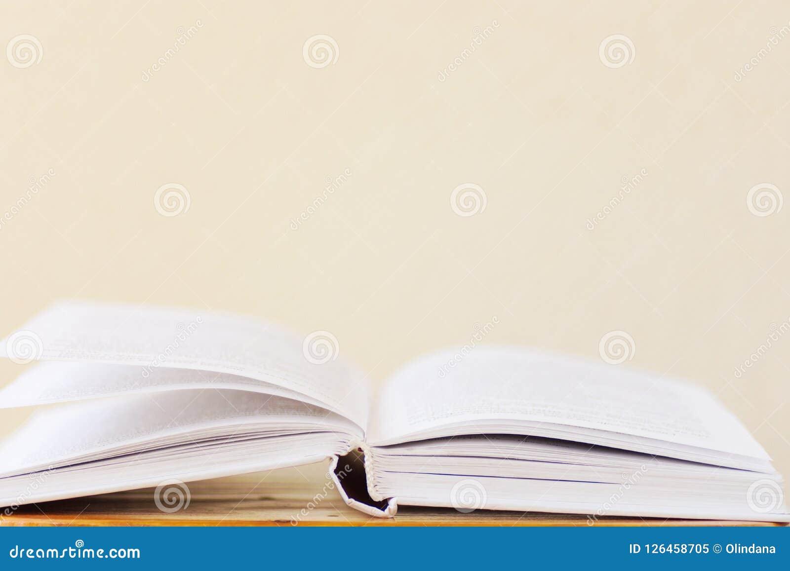 Libro aperto che si trova sul fondo bianco della parete dello spazio in bianco di legno della tavola Istruzione dell università d