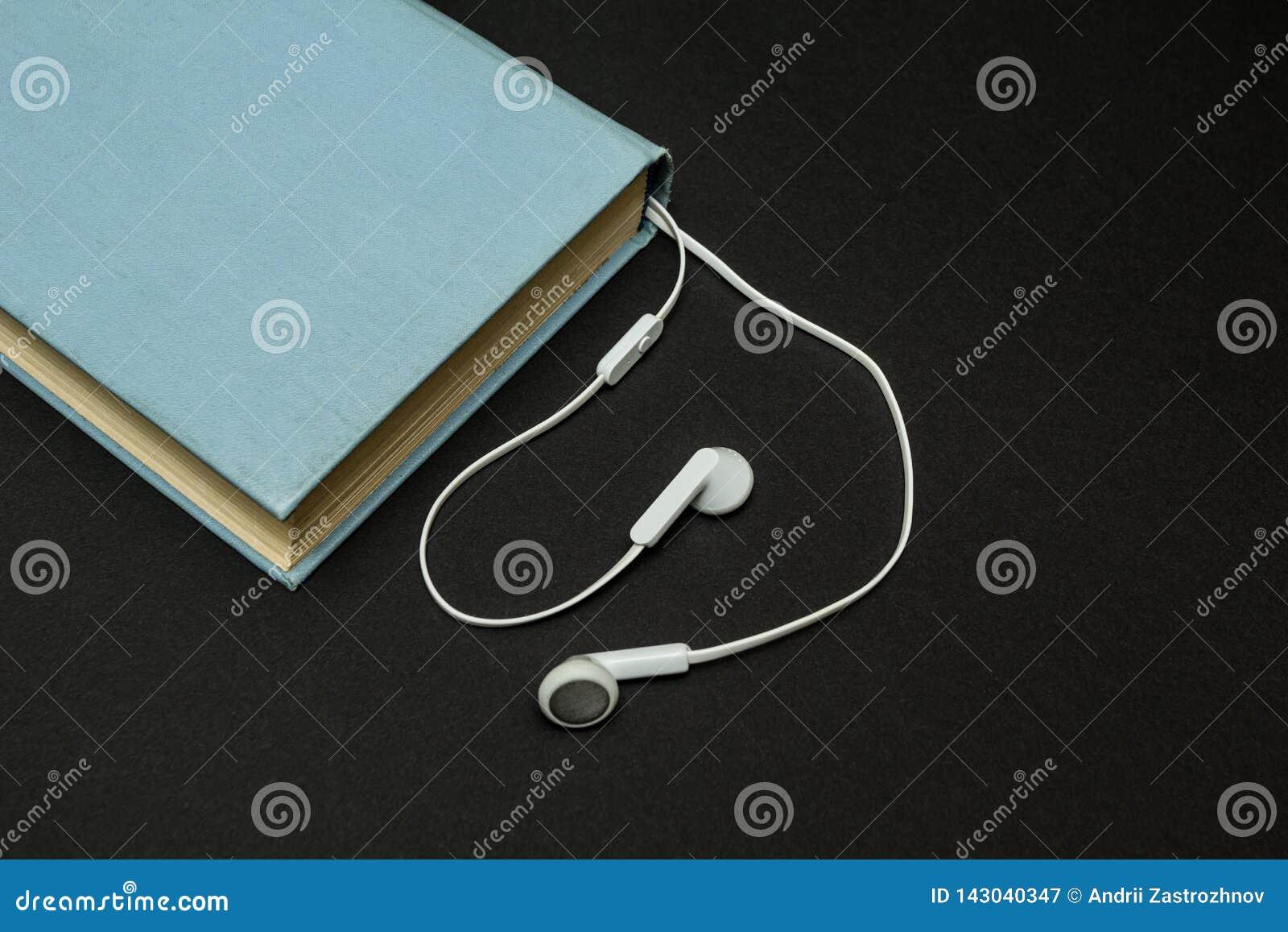 Libro azul viejo, y auriculares blancos en un fondo negro