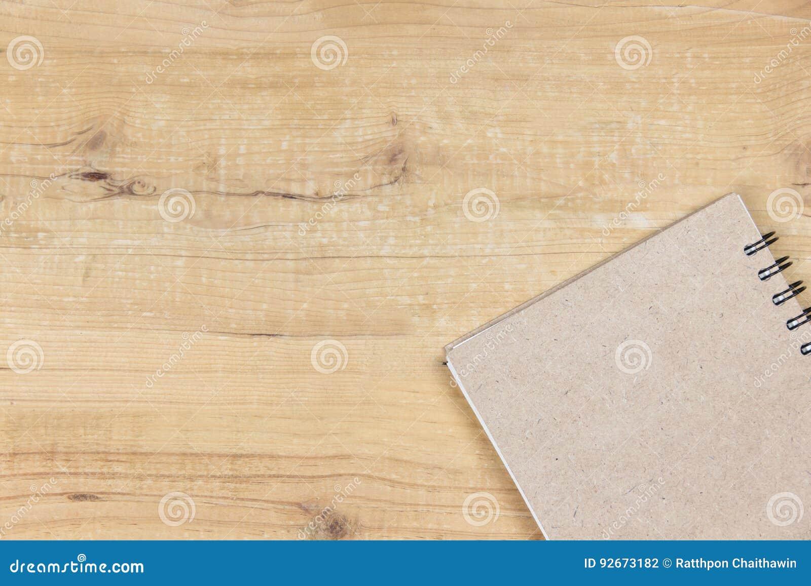 Libro de la cubierta en el escritorio de madera Fondo de la visión superior