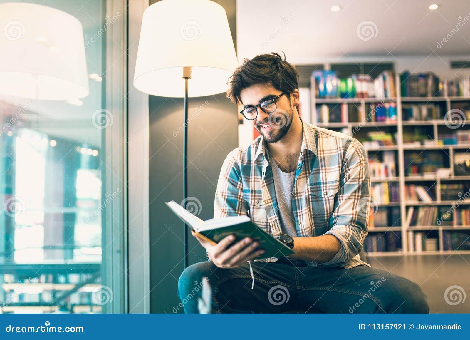 Libro de lectura del hombre en la biblioteca