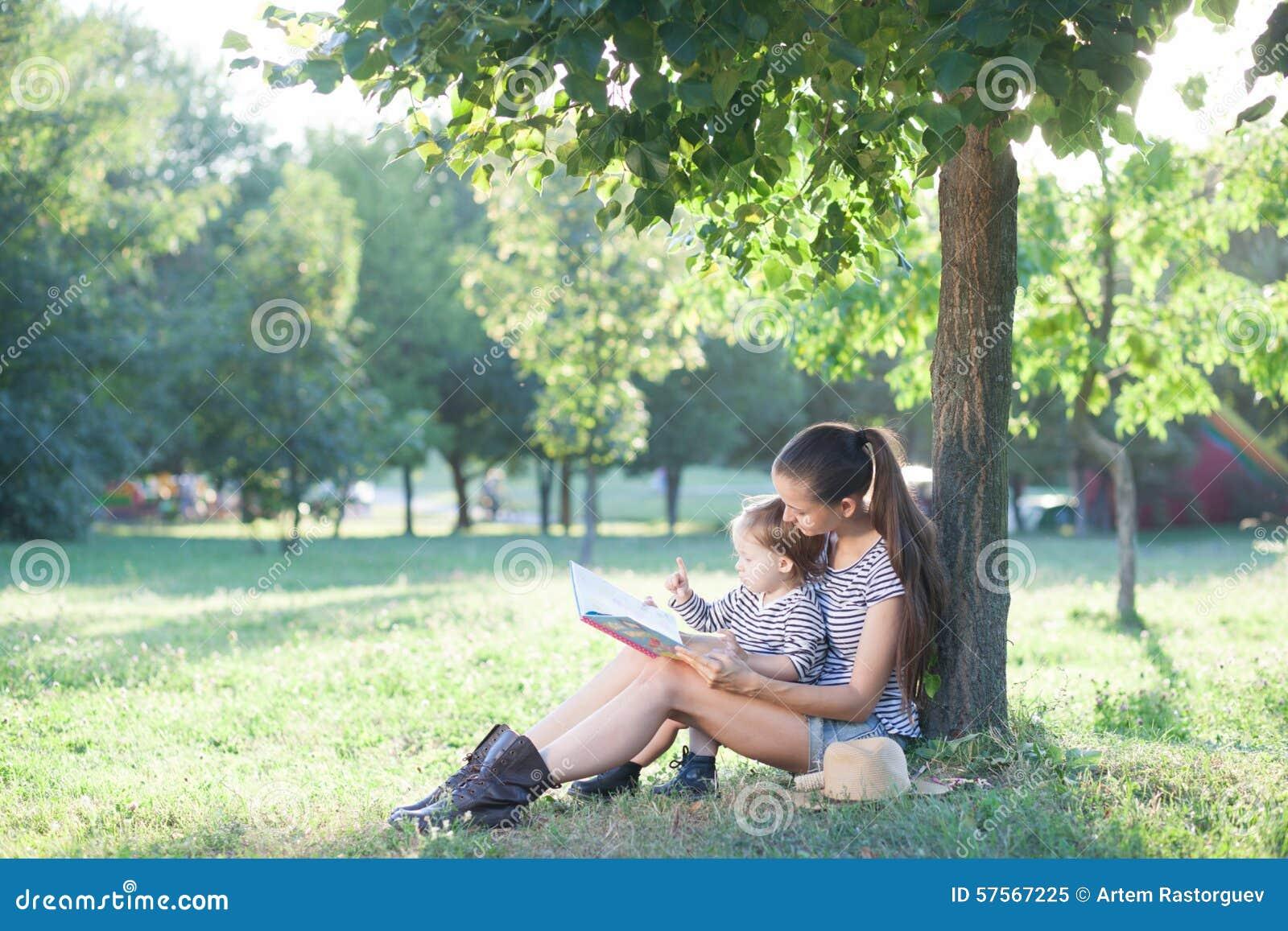 Libro de lectura elegante de la madre y del niño en el jardín durante la diversión del verano