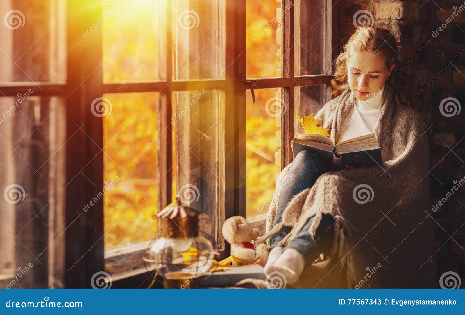 Libro de lectura feliz de la mujer joven por la ventana en caída