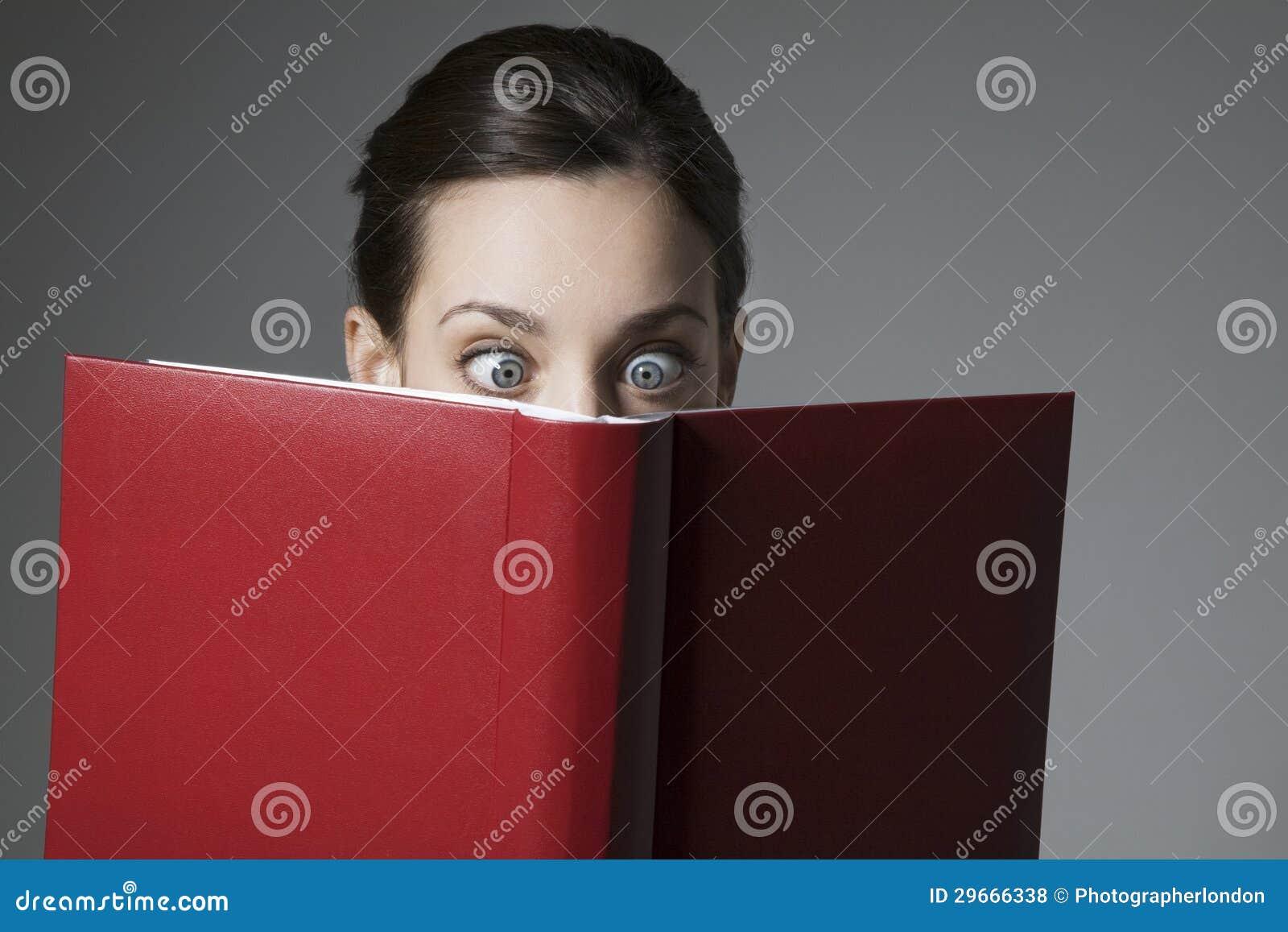 Libro de lectura femenino joven asombroso con los ojos abiertos de par en par