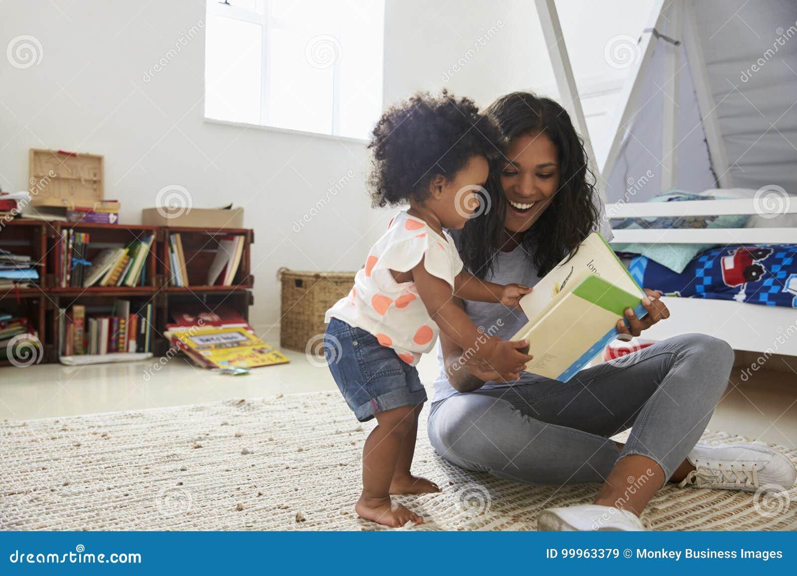 Libro de lectura de la hija de la madre y del bebé en sala de juegos junto