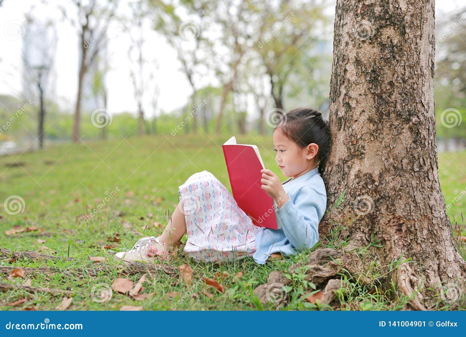 Libro de lectura lindo de la niña en magro al aire libre del parque del verano contra tronco de árbol en el jardín del verano