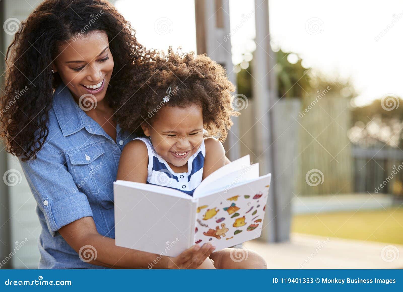 Libro de lectura negro joven de la muchacha que se sienta en rodilla del ½ s del ¿del mumï al aire libre