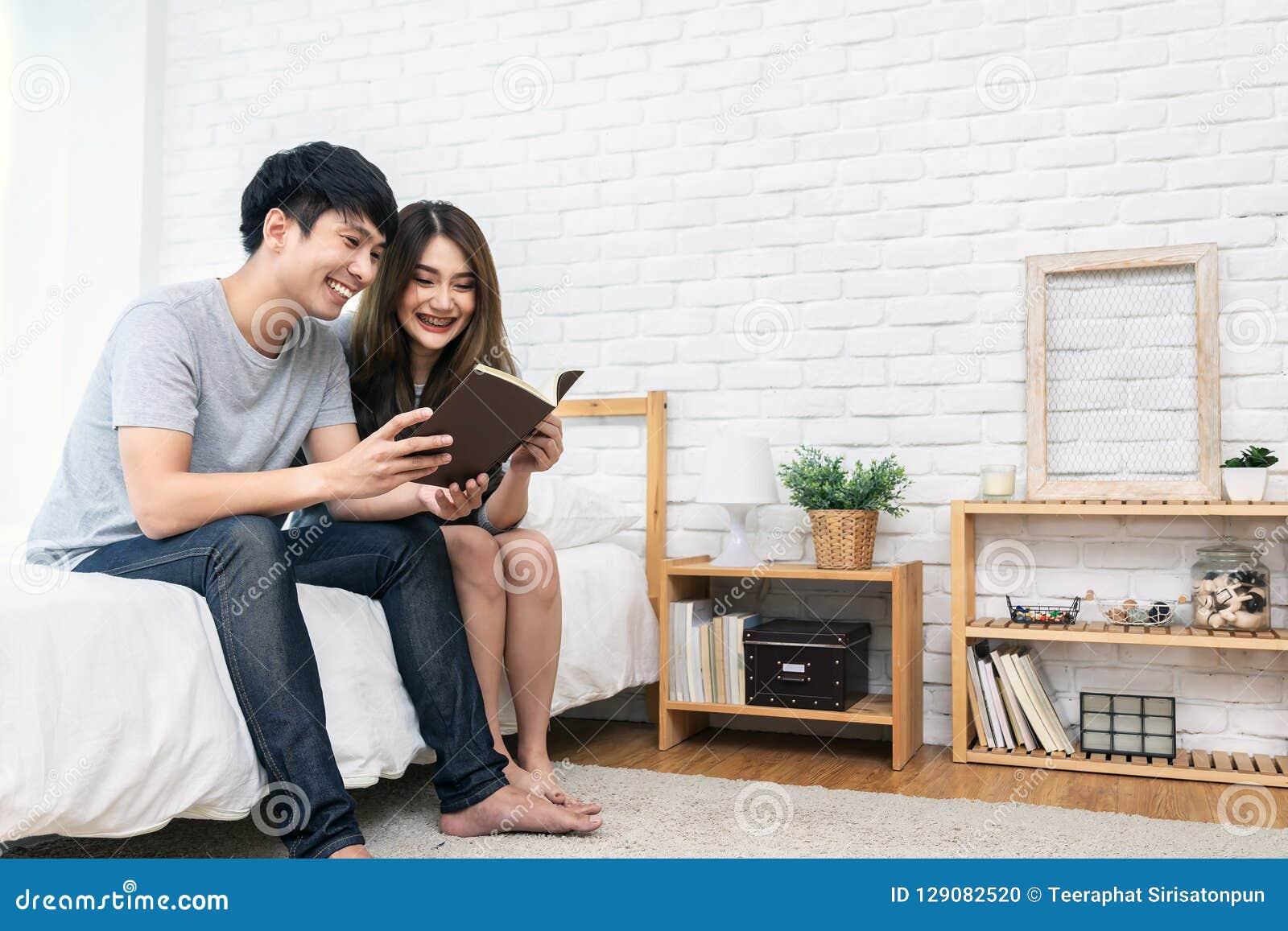 Libro de lectura romántico asiático joven de los pares que tiene gran tiempo junto que siente la satisfacción y el positivo en el
