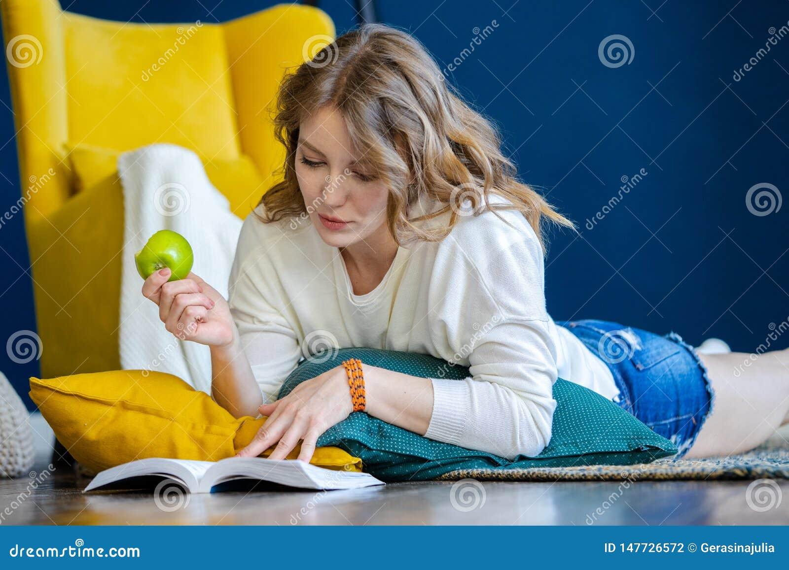 Libro de lectura rubio de la mujer en casa y poniendo en el piso al lado de la butaca amarilla