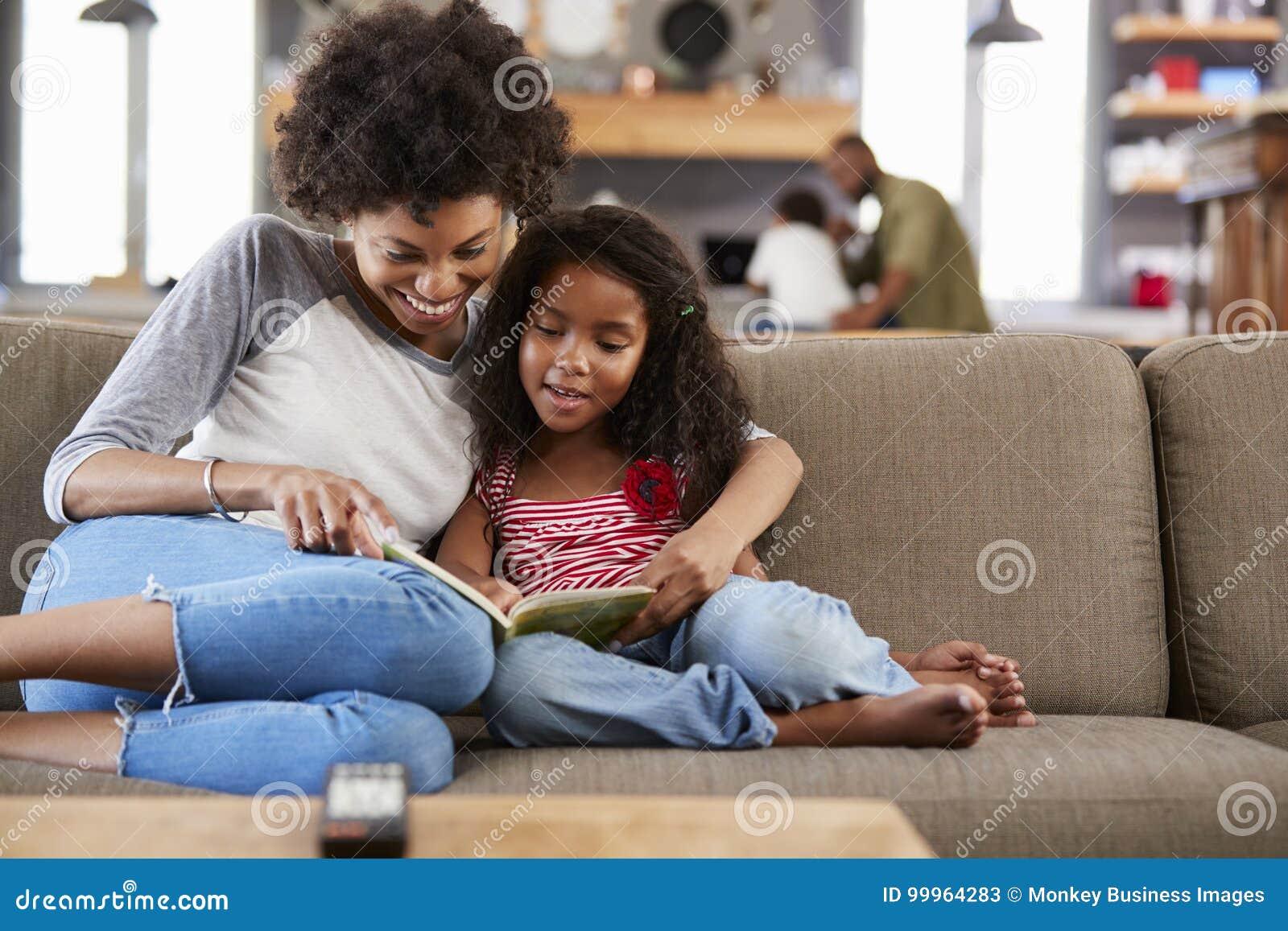 Libro de lectura de Sit On Sofa In Lounge de la madre y de la hija junto
