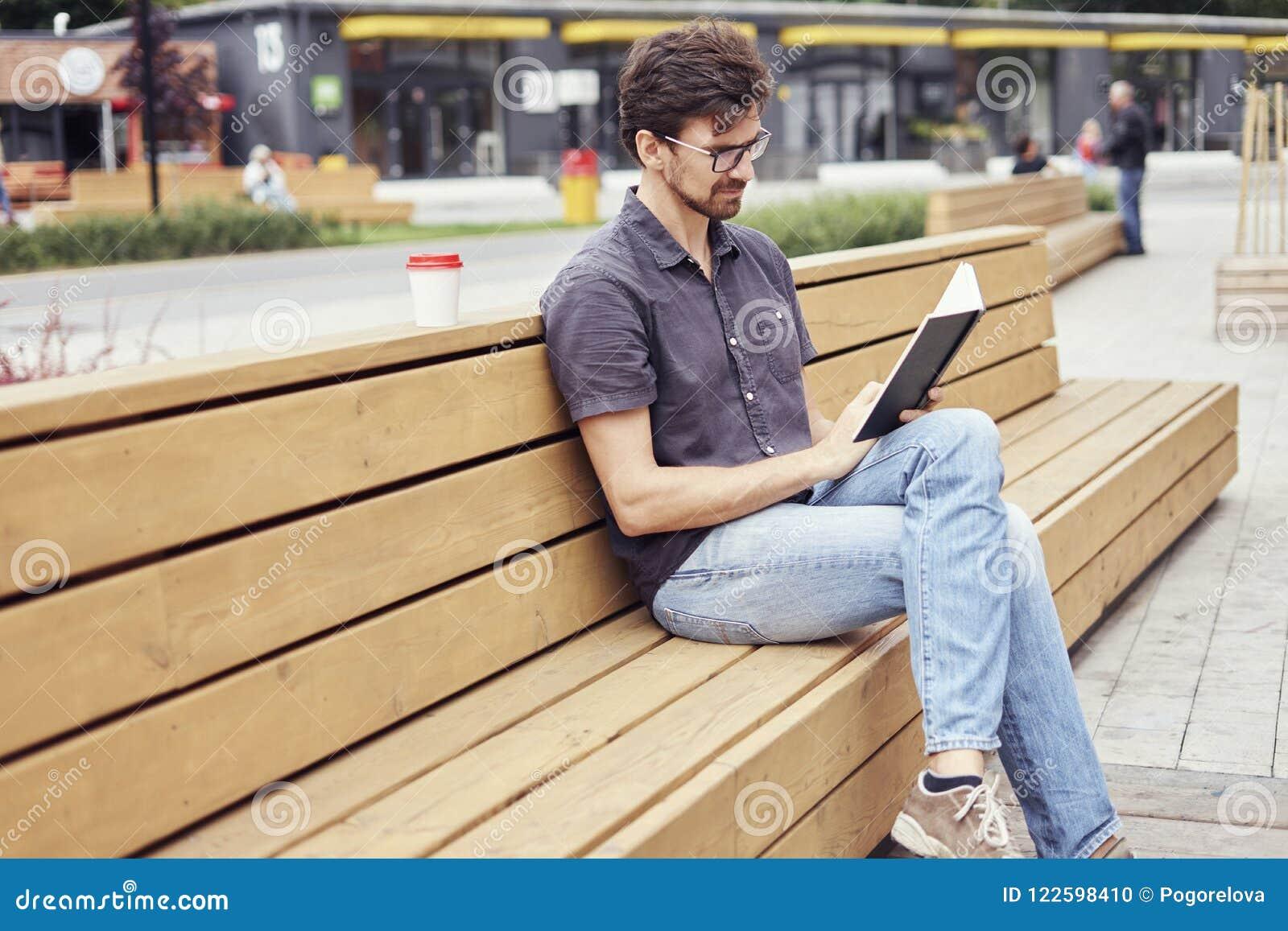 Libro di lettura bello dell uomo che si siede fuori nello spazio pubblico Lavoro solo d uso di vetro Concetto degli studenti di i