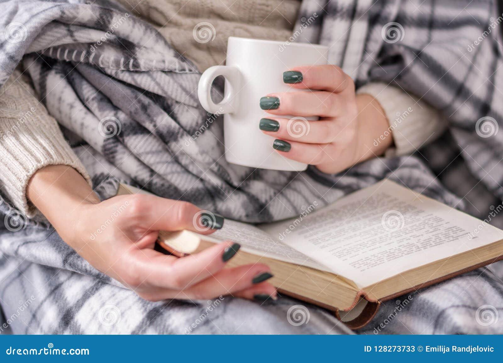 Libro di lettura della ragazza e tazza di caffè della tenuta e coperto di retro coperta