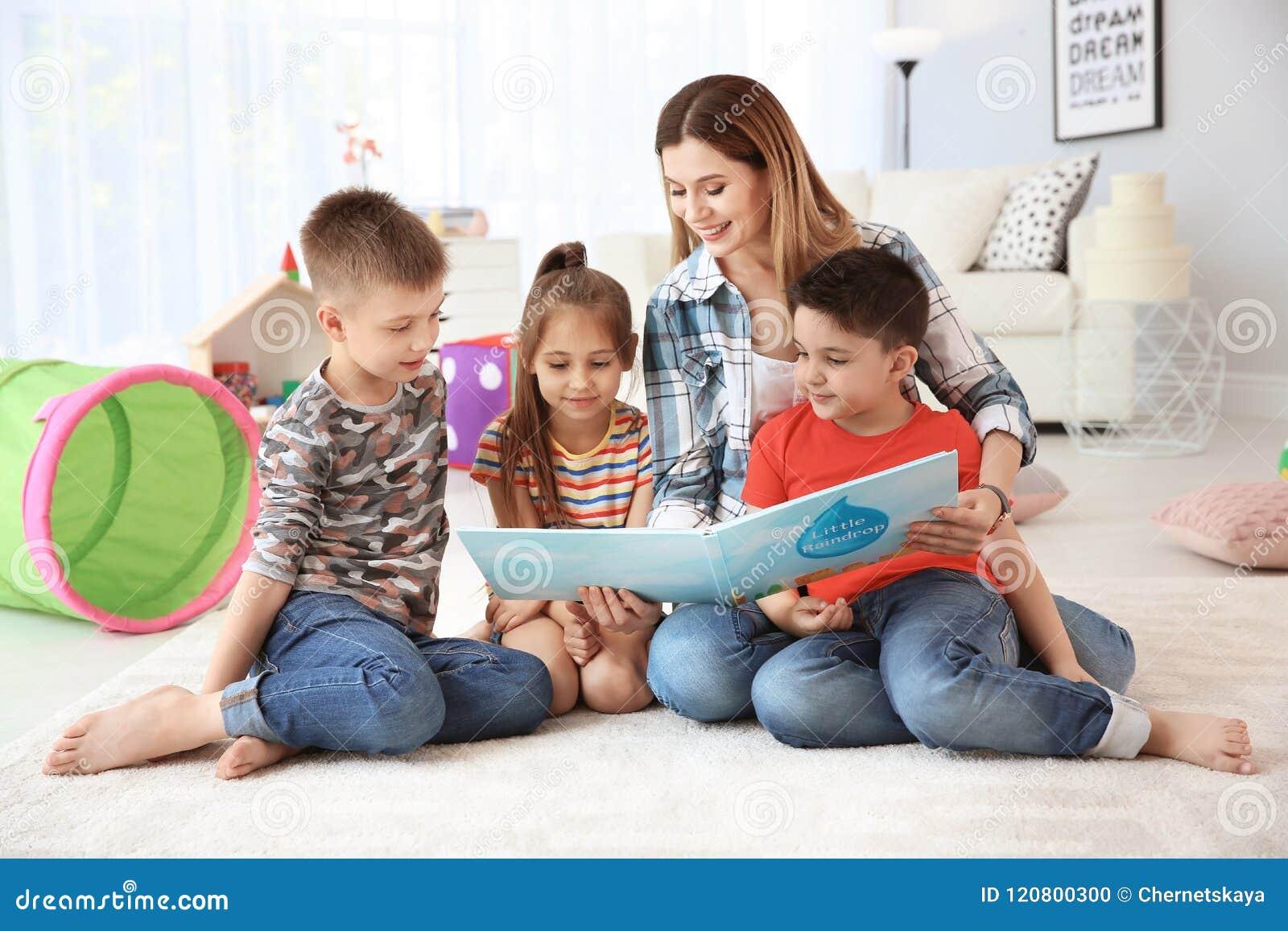 Libro di lettura sveglio dei piccoli bambini sul pavimento